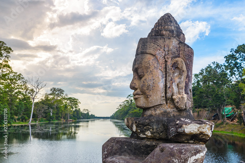 Photo Stands Place of worship Stone faces in Bayon, Angkor Thom temple, selective focus sunset light. Buddhism meditation concept, world famous travel destination, Cambodia tourism.