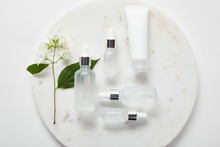 Top View Of Cream Tube And Cosmetic Glass Bottles In Plate With Jasmine On White Surface