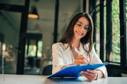 Smiling young woman filling application form or writing personal information in contract. - fototapety na wymiar