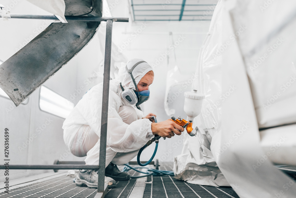 Fototapety, obrazy: Side view of a professional painter painting a car in a paint chamber.