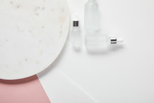 Top View Of Cosmetic Glass Bottles Near Plate On White Pink Surface