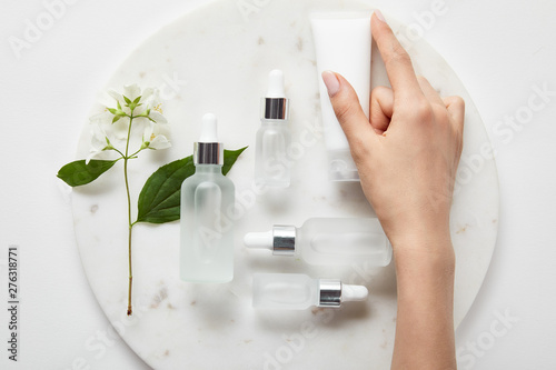 Fotografie, Obraz cropped view of woman hand with cream tube over plate with jasmine and cosmetic