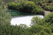 Water Spills Over The Top Of Louros River Hydroelectric Dam In A Green Forest In Epirus, Greece Near The Town Of Filippiada