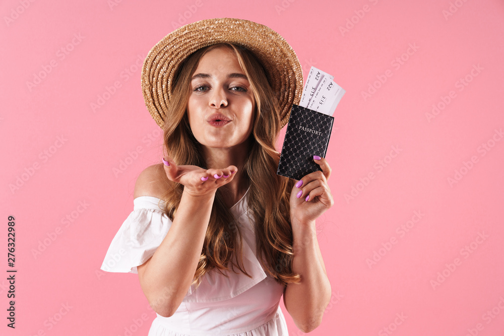 Fototapety, obrazy: Pleased young pretty woman posing isolated over pink wall background holding passport with tickets blowing kisses.