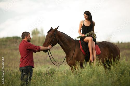 Photo  A young couple walks during horseback riding.
