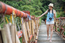 Full Length Young Asian Female Tourist Bamboo Tube For Wishing At Pingxi Old Street Wood Bridge. Girl Traveler In Hat Carry Professional Camera Travel In Nature Forest Taipei Taiwan. Woman In Summer.