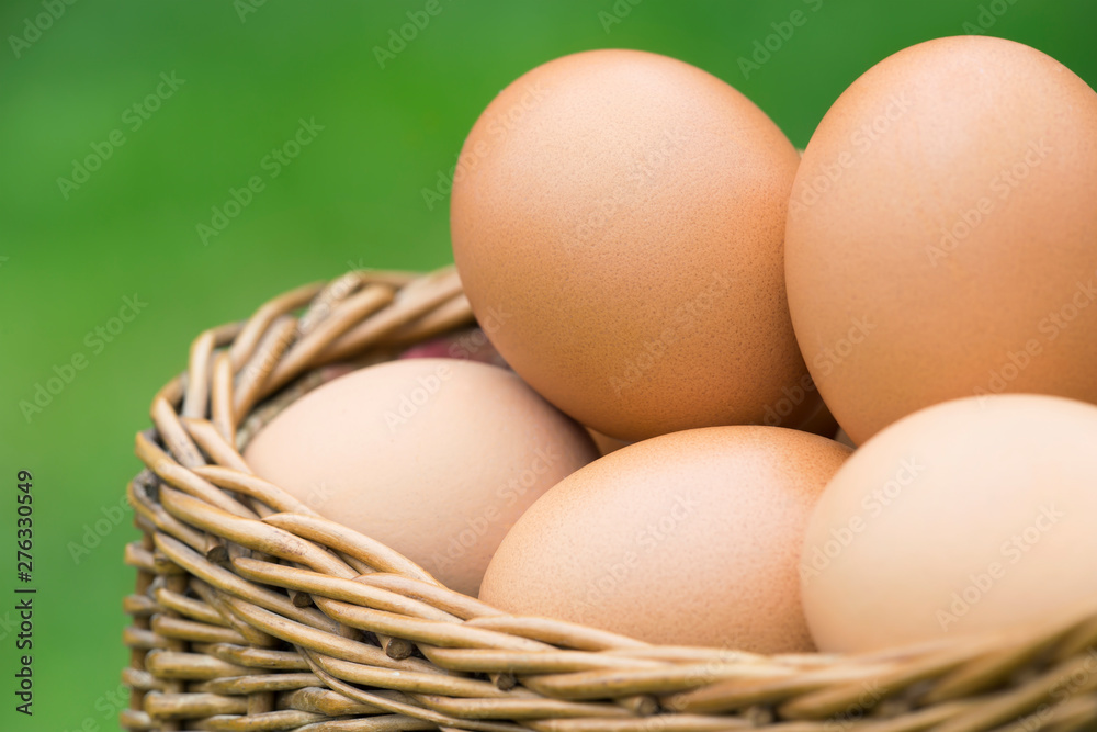 Fototapety, obrazy: Close-up of fresh eggs in a basket on green background