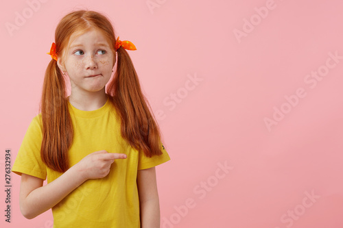 Little thinking freckles red-haired girl with two tails