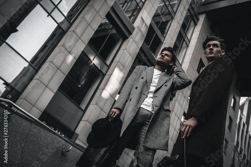 Fotografía  Bearded men in full suit and coat walking on city street in casual and classic clothes with cane and stylish hairstyle
