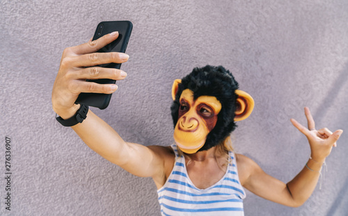 Valokuva  Crazy young woman with monkey mask stands on a gray wall and use a smartphone to take a selfie pic