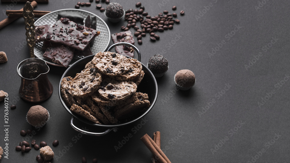 Fototapety, obrazy: Chocolate truffles and healthy oats cookies in utensil on black backdrop
