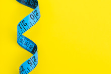 Health Fitness, Nutrition, Exercise Or Diet Concept, Blue Measuring Tape On Solid Yellow Background With Copy Space Using As Measurement
