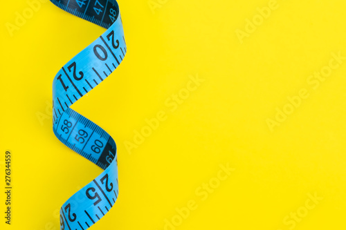 Obraz Health fitness, nutrition, exercise or diet concept, blue measuring tape on solid yellow background with copy space using as measurement - fototapety do salonu