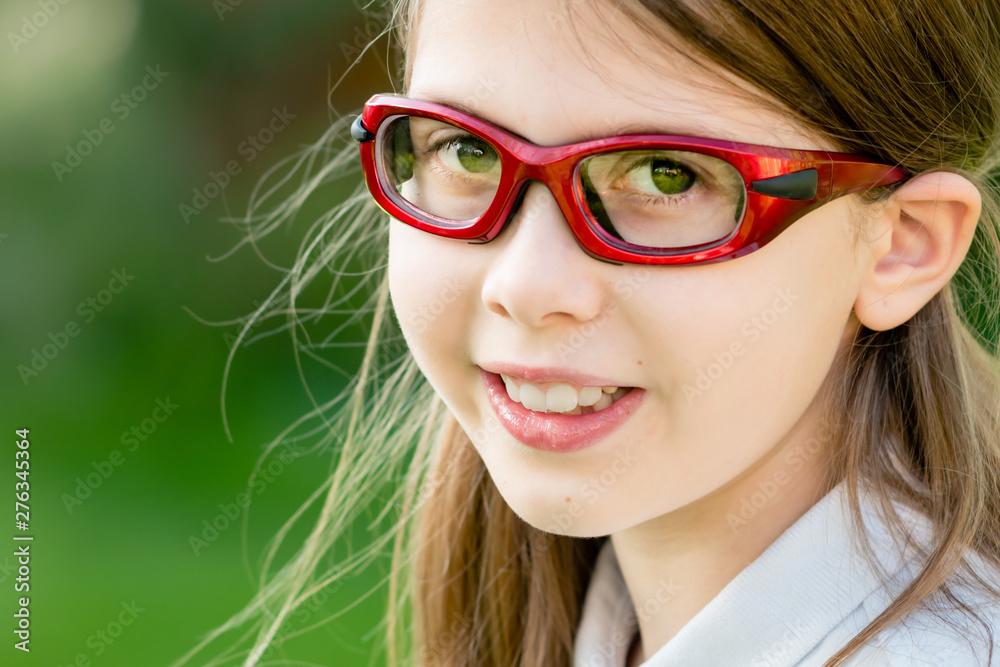 Fototapeta Close-up portrait of a girl child wearing red prescription sports glasses or goggles