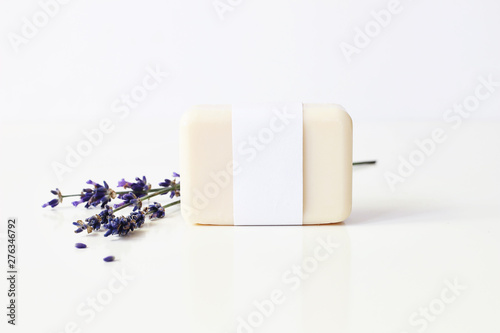 Poster Pierre, Sable Closeup of hand made herbal soap bar in blank paper label package and bunch of lavender flowers on white table backround. Spa concept. Skin product mockup scene. Cosmetic product.