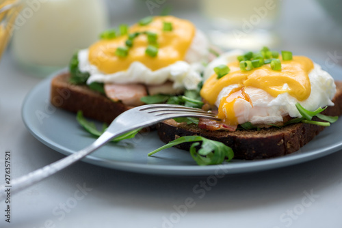 Close up eggs Benedict with arugula, bacon and hollandaise sauce on gray wooden background Fototapeta