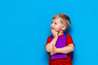 Leinwanddruck Bild - Back to school Portrait of happy surprised kid in glasses isolated on blue background with copy space. new school knowledges