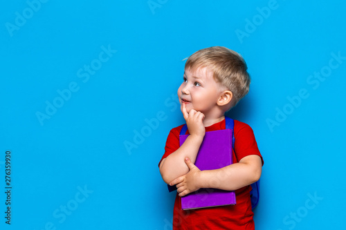 Fotomural Back to school Portrait of happy surprised kid in glasses isolated on blue background with copy space