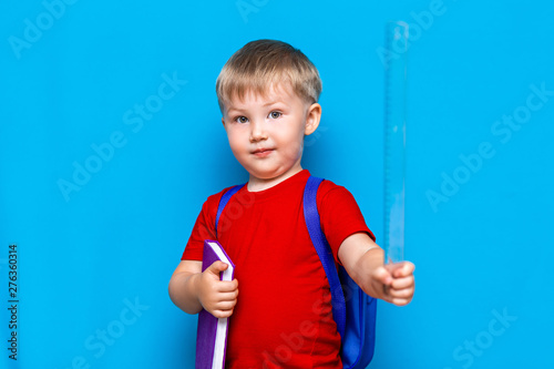 Fotomural  small happy smiling boy with glasses on his head, book in hands, schoolbag on his shoulders