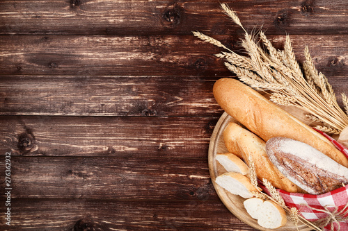 Foto auf Leinwand Brot Fresh baguettes with wheat ears on brown wooden table