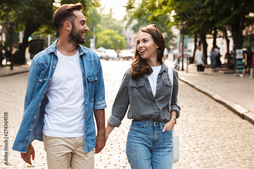 Beautiful young couple in love walking outdoors at the city street Canvas Print