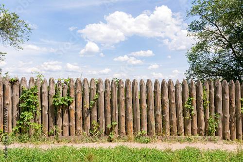 Photo  Old fence of logs. Palisade against the blue sky