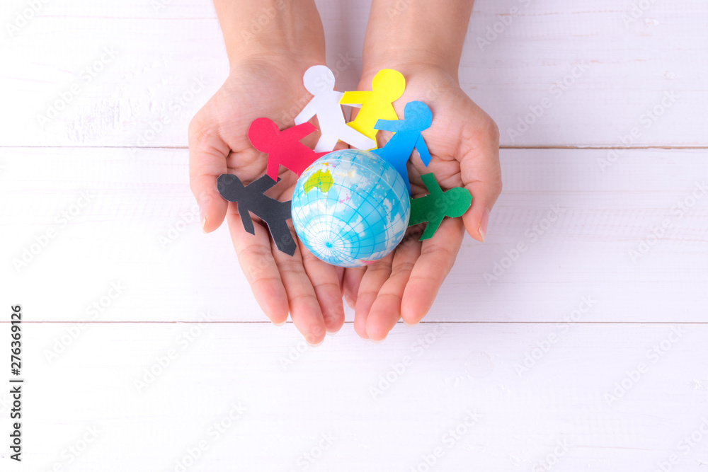 Fototapeta Woman holding globe with people chain made from paper cut. World population day.