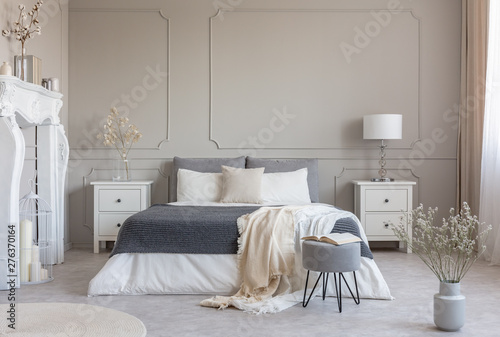 Fototapeta Flowers on white wooden nightstand table in luxury bedroom interior with king size bed obraz