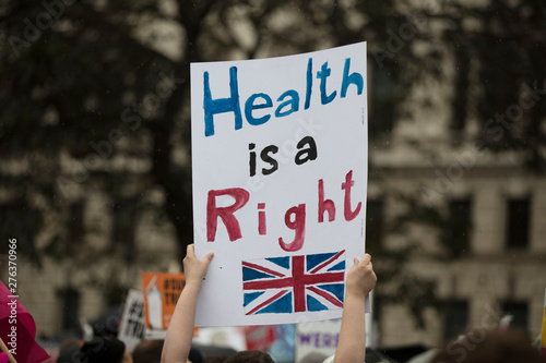 Photo A protestor holds a political banner with health is a human right message