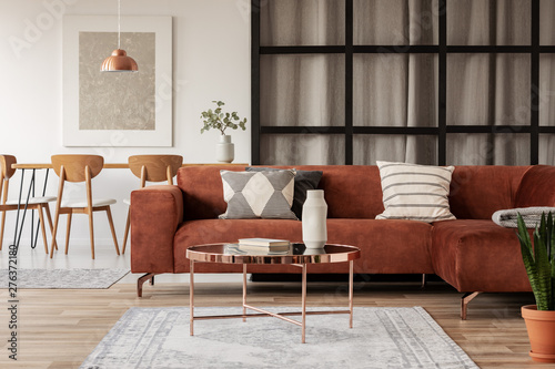 Stylish brown corner sofa with patterned pillows in elegant living room interior with mullions wall - 276372180