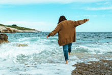 Woman Walking By Rocky Sea Beach At Sunny Windy Day. Summer Vacation