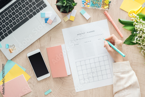 Obraz cropped view of woman sitting behind wooden table with smartphone, laptop and stationery, writing in monthly planner - fototapety do salonu