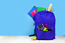 Purple Backpack Full Of School Supplies Against A Blue Background. Back To School Concept. Copy Space.