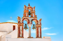 Beautiful Old Orthodox White Church With Blue Dome And The Old Arch With Bells Against The Blue Sky, Santorini, Greece, Europe. Classic White Greek Architecture, Houses, Churches. Travel Concept