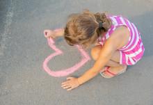 Child Paints Chalk On The Asphalt Heart. Selective Focus.