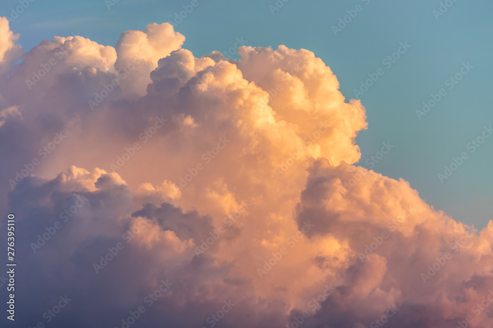 Fototapeta Close up view of beautiful colored dramatic cumulus fluffy clouds on blue sky at sunset background