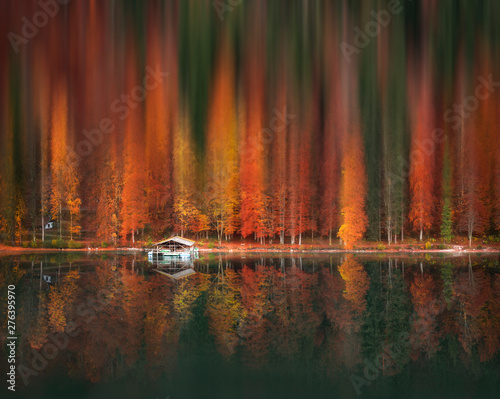 Motion blur autumn forest and water reflection