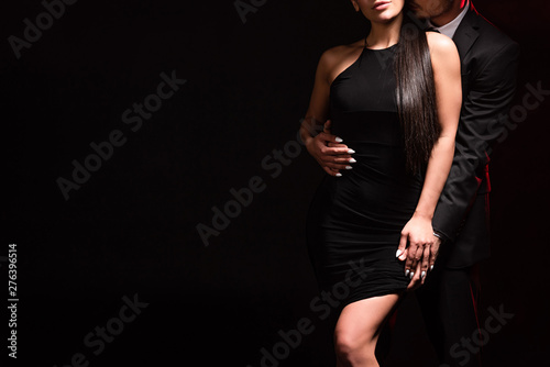 Photo  cropped view of elegant couple embracing on black