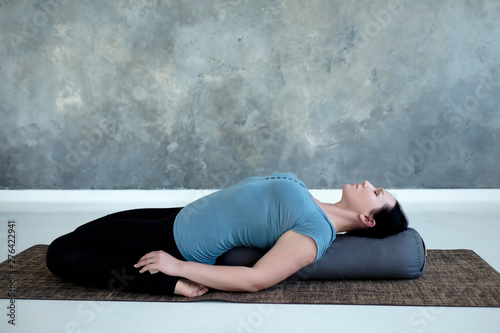 Cauacasian woman resting in reclining hero pose or Supta Virasana with bolster, stretching after practice Wallpaper Mural