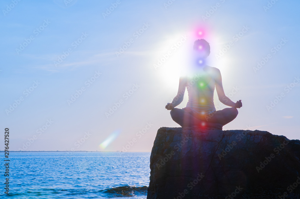 Fototapety, obrazy: Woman is meditating with glowing seven chakras on stone at sunset. Silhouette of woman is practicing yoga on the beach.