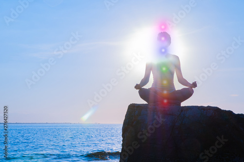 Fotografie, Obraz  Woman is meditating with glowing seven chakras on stone at sunset