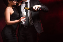 Cropped View Of Man In Formal Wear Pouring Champagne To Woman In Dress And Mask On Black