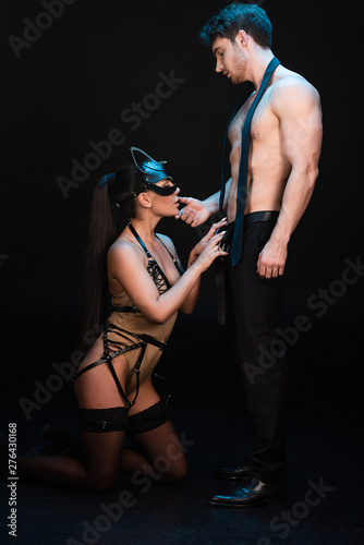 full length view of erotic bdsm couple on black