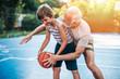 Leinwandbild Motiv Grandfather and his grandson playing basketball.