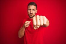 Young Handsome Man Wearing Casual T-shirt Over Red Isolated Background Punching Fist To Fight, Aggressive And Angry Attack, Threat And Violence