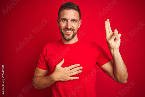 Fotografia  Young handsome man wearing casual t-shirt over red isolated background smiling s