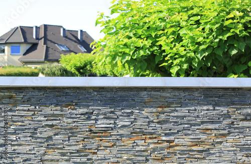 Obraz Murowane ogrodzenie z kamienia, dach budynku i zielone drzewa. - fototapety do salonu
