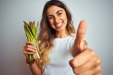 Young Beautiful Woman Eating Asparagus Over Grey Isolated Background Happy With Big Smile Doing Ok Sign, Thumb Up With Fingers, Excellent Sign