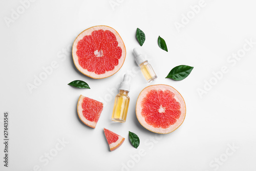 Stampa su Tela Composition with grapefruit slices and bottles of essential oil on white backgro