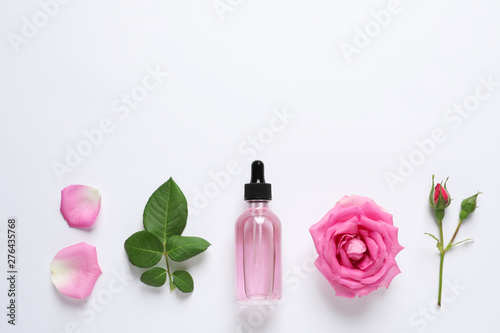 Fotografie, Obraz  Composition with rose essential oil and flowers on white background, top view
